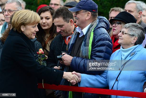 German Chancellor Angela Merkel shakes hands with a visitor as she arrives for a commemoration to mark the 25th anniversary of the fall of the Berlin...