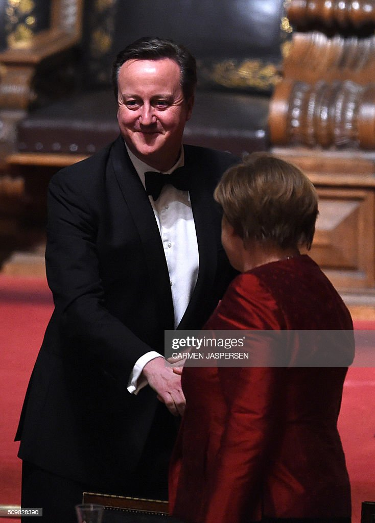 German Chancellor Angela Merkel (R) shakes hands with British Prime Minister David Cameron after his speech at the Matthiae-Mahr Dinner in Hamburg, northern Germany on February 12, 2016. / AFP / CARMEN JASPERSEN