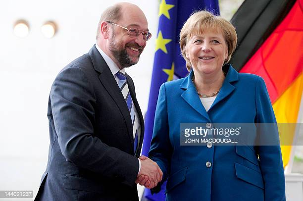 German chancellor Angela Merkel shakes hands with European Parliament President Martin Schulz as he arrives for a meeting at the Chancellery on May 8...