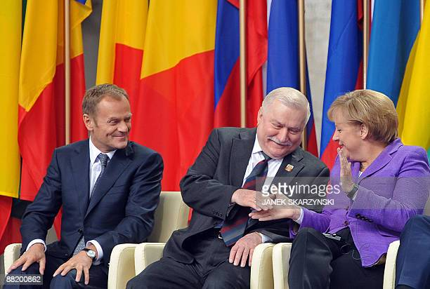German Chancellor Angela Merkel shakes hands with former Polish President Lech Walesa the iconic Solidarity union leader next to Polish Prime...