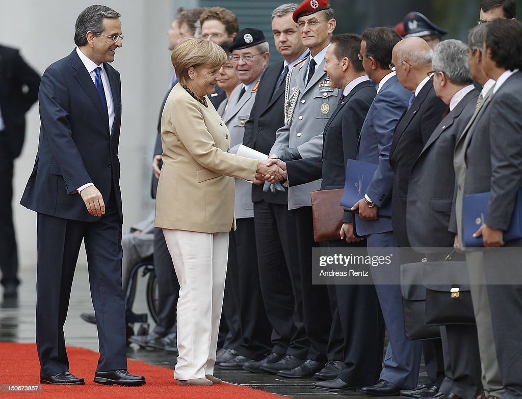 German Chancellor <a gi-track='captionPersonalityLinkClicked' href=/galleries/search?phrase=Angela+Merkel&family=editorial&specificpeople=202161 ng-click='$event.stopPropagation()'>Angela Merkel</a> (2nd-L) shakes hands with Greek Finance Minister Yannis Stournaras as Greek Prime Minister <a gi-track='captionPersonalityLinkClicked' href=/galleries/search?phrase=Antonis+Samaras&family=editorial&specificpeople=970799 ng-click='$event.stopPropagation()'>Antonis Samaras</a> (L) smiles upon Samaras arrival at the Chancellery on August 24, 2012 in Berlin, Germany. Samaras is in Berlin to discuss the conditions of Greece's financial bailout after announcing previously that he is seeking more time for his country to push through required economic reforms in the face of its debt crisis.