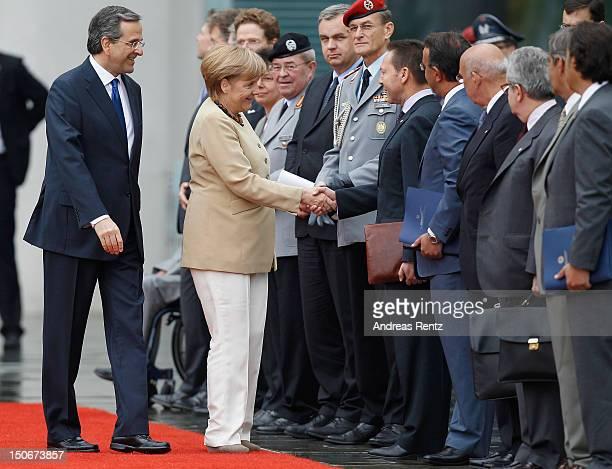 German Chancellor Angela Merkel shakes hands with Greek Finance Minister Yannis Stournaras as Greek Prime Minister Antonis Samaras smiles upon...