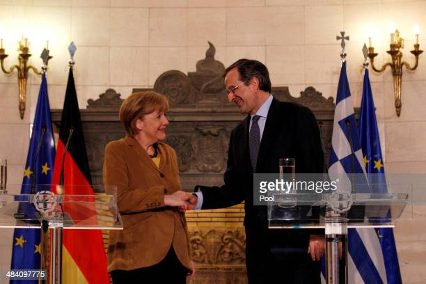German Chancellor Angela Merkel shakes hands with Greek Prime Minister Antonis Samaras after a news conference following their meeting on April 11...