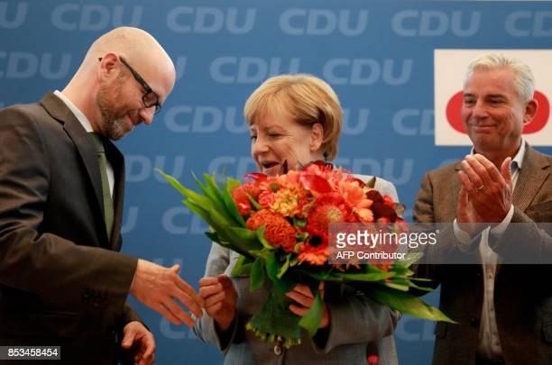 German Chancellor Angela Merkel shakes hands with her conservative Christian Democratic Union party's secretary general Peter Tauber as they arrive...