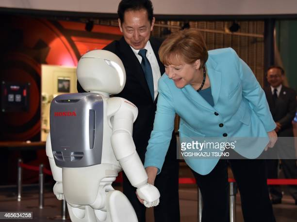 German Chancellor Angela Merkel shakes hands with Japanese auto giant Honda Motor's humanoid robot Asimo as museum head and former astronaut Mamoru...