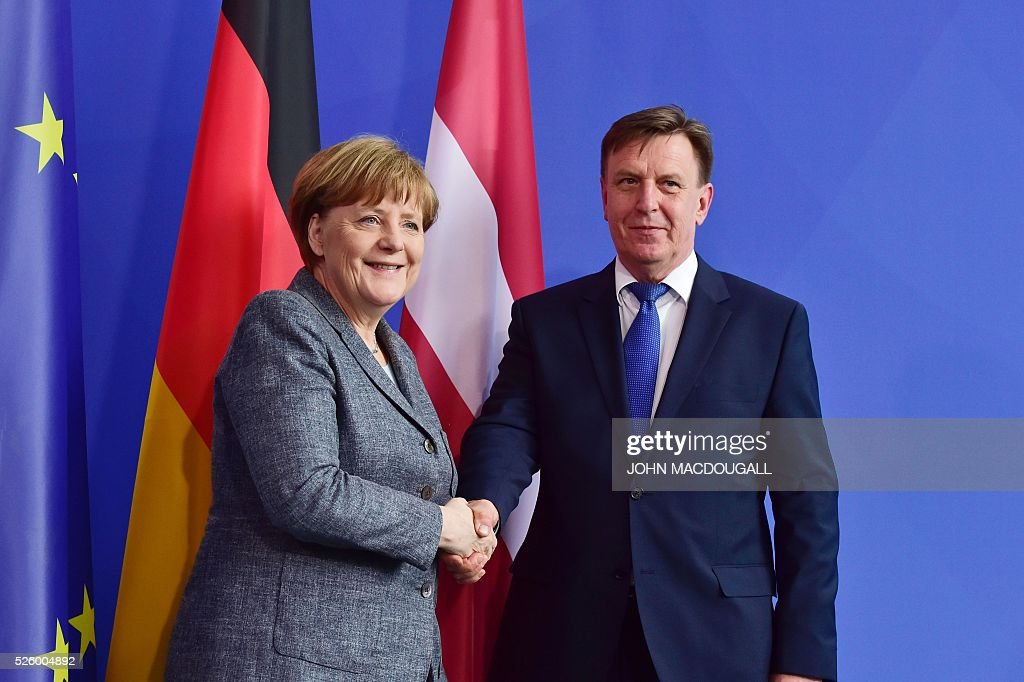 German Chancellor Angela Merkel (L) shakes hands with Latvian Prime Minister Maris Kucinskis after a joint press conference in Berlin, on April 29, 2016. / AFP / John MACDOUGALL