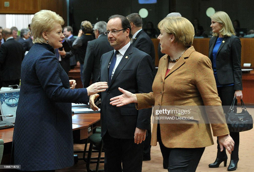 German Chancellor Angela Merkel (R) shakes hands with Lithuanian President Dalia Grybauskaite as French President Francois Hollande looks on at the EU Headquarters on November 22, 2012 in Brussels, during a two-day European Union leaders summit called to agree a hotly-contested trillion-euro budget through 2020. European Union officials were scrambling to find an all but impossible compromise on the 2014-2020 budget that could successfully move richer nations looking for cutbacks closer to poorer ones who look to Brussels to prop up hard-hit industries and regions.
