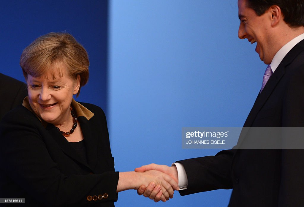 German Chancellor Angela Merkel shakes hands with Lower Saxony's State Premier David McAllister at the beginning of a congress of Germany's ruling conservative Christian Democratic Union (CDU) party on December 4, 2012 in Hanover, central Germany. Germany's Angela Merkel will rally the rank-and-file of her conservative party at its annual congress running until December 5, eyeing a third term as chancellor of Europe's top economy in elections in the year 2013.