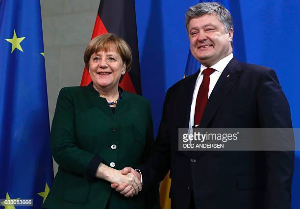 German Chancellor Angela Merkel shakes hands with Ukraine's President Petro Poroshenko following a press statement prior to their talks at the...