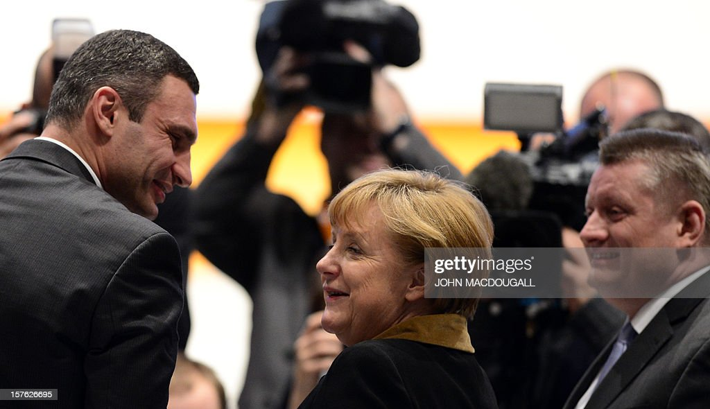 German Chancellor Angela Merkel shakes hands with Ukrainian box champion and member of Ukrainian Parliament Vitali Klitschko (L) as CDU Secretary General Hermann Groehe (R) looks on during a congress of Germany's ruling conservative Christian Democratic Union (CDU) party on December 4, 2012 in Hanover, central Germany. German Chancellor Angela Merkel was re-elected head of her conservative Christian Democrats (CDU) by more than 97 percent of delegates' votes at a two-day party congress. It was Merkel's best result since she took over as chairman of the CDU in 2000 and comes as she gears up for fighting for a third term at the helm of Europe's top economy in elections expected in September 2013.