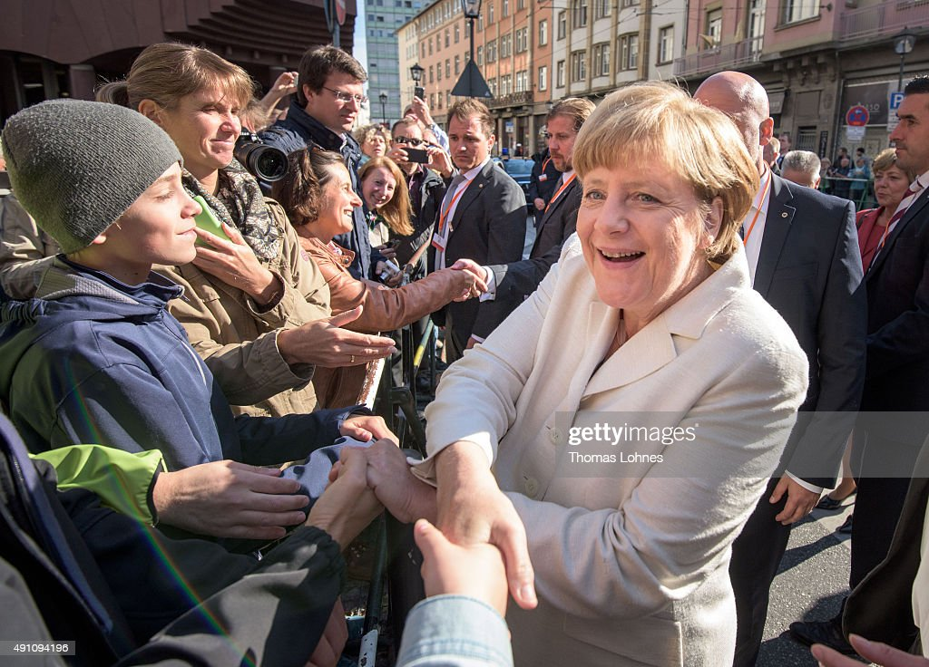 German Chancellor <a gi-track='captionPersonalityLinkClicked' href=/galleries/search?phrase=Angela+Merkel&family=editorial&specificpeople=202161 ng-click='$event.stopPropagation()'>Angela Merkel</a> shakes the hand of a spectator after visiting a church service at 'Kaiserdom' to celebrate the 25th anniversary of German reunification on October 3, 2015 in Frankfurt, Germany. On October 3, 1990, following the end of the Cold War, western-oriented, capitalist and democratic West Germany and post-revolution, formerly communist East Germany reunited into a single state after 41 years of official separation. Though the integration of the two former states into one is seen by most as a success, differences remain, particularly in average incomes and pensions, which in eastern Germany are lower.