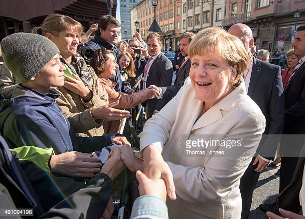 German Chancellor Angela Merkel shakes the hand of a spectator after visiting a church service at 'Kaiserdom' to celebrate the 25th anniversary of...