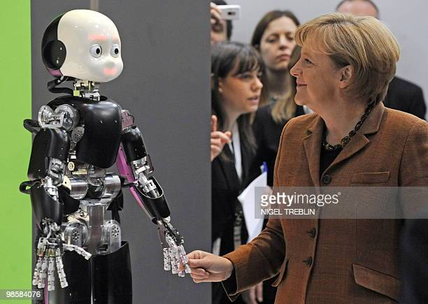German Chancellor Angela Merkel shakes the hand of robot 'iCub' at the stand of this year's partner country Italy during her opening tour of the...
