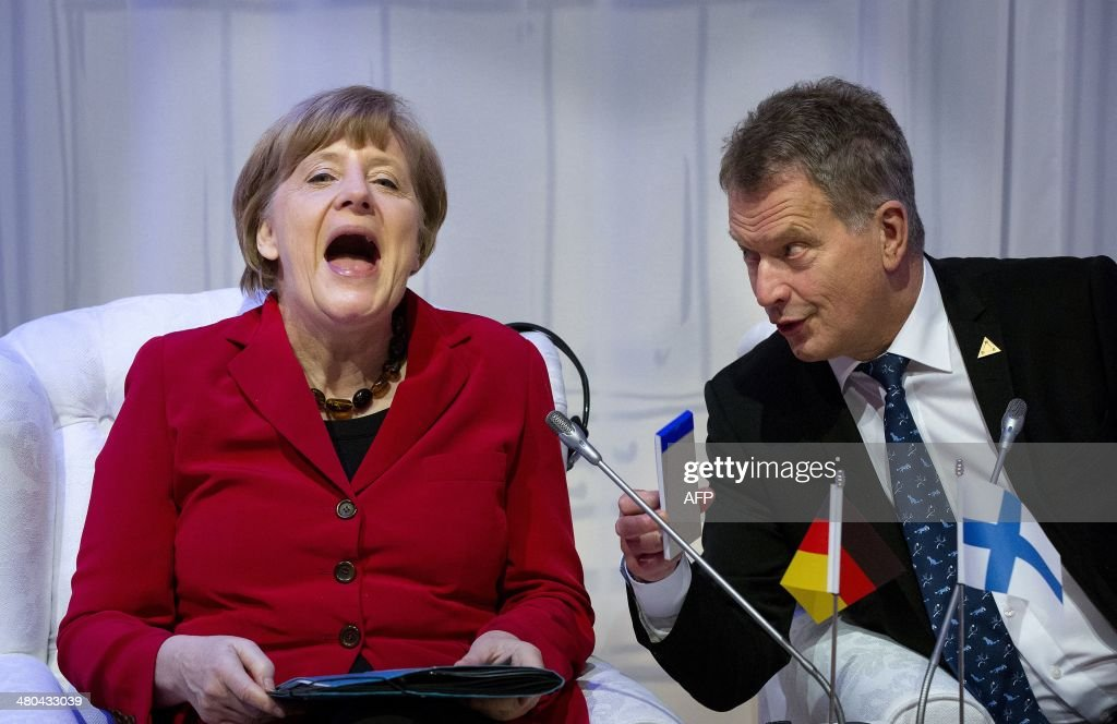 German Chancellor Angela Merkel (L) shares a laugh with Finnish President Sauli Niinisto during an informal plenary session in The Hague on March 25, 2014 on the second day of the two-day Nuclear Security Summit (NSS). The world must construct a system to fight nuclear terror with the world's atomic watchdog playing a central role, a draft of the Nuclear Security Summit's final statement says. / AFP / POOL / Bart Maat