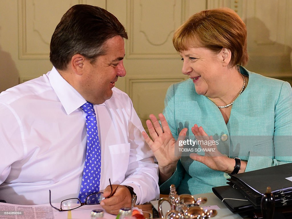 German Chancellor Angela Merkel shares a smile with German Vice Chancellor, Economy and Energy Minister Sigmar Gabriel prior to the weekly cabinet meeting taking place in the framework of a retreat meeting of the German cabinet at Meseberg Palace on May 25, 2016 in Meseberg near Gransee, northeastern Germany. / AFP / TOBIAS