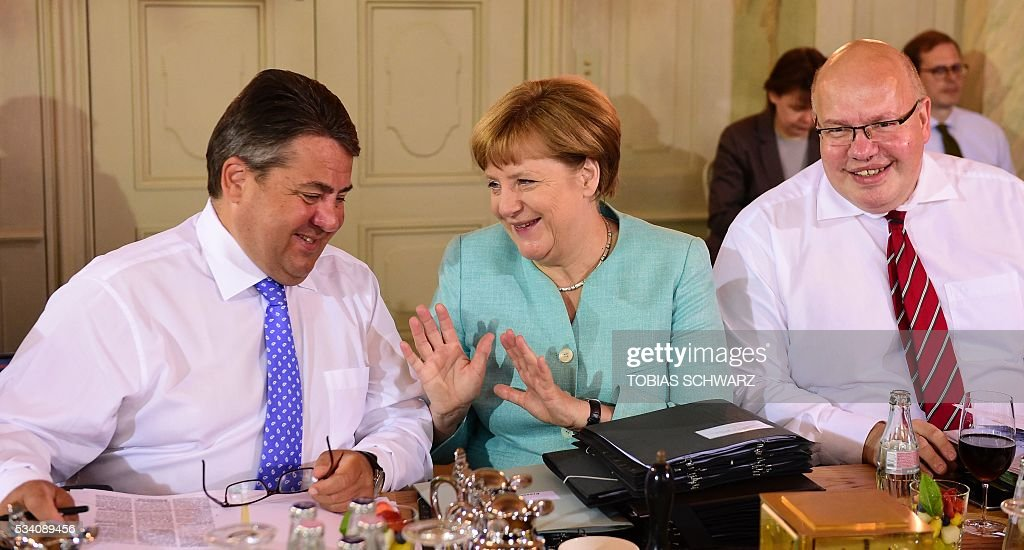German Chancellor Angela Merkel (C) shares a smile with German Vice Chancellor, Economy and Energy Minister Sigmar Gabriel (L) as German Chief of Staff Peter Altmaier (R) looks on prior to the weekly cabinet meeting taking place in the framework of a retreat meeting of the German cabinet at Meseberg Palace on May 25, 2016 in Meseberg near Gransee, northeastern Germany. / AFP / TOBIAS