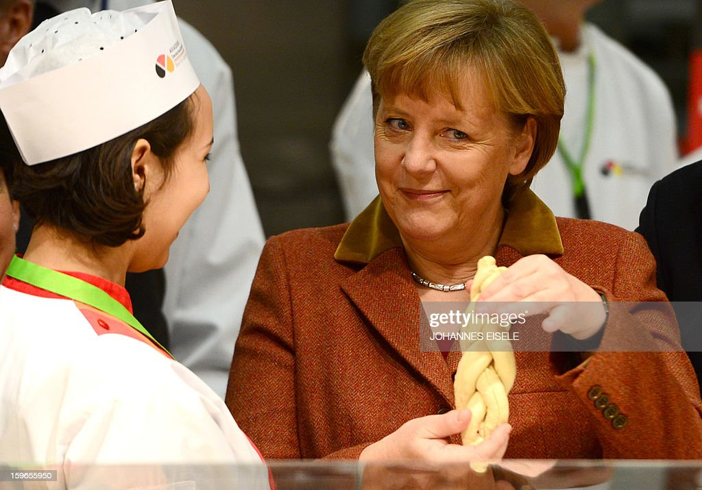 German Chancellor Angela Merkel shows a bread she made at a bakery and pastry booth as she opens the Gruene Woche Agricultural Fair in Berlin on January 18, 2013. This year the official partner country of the fair is The Netherlands. EISELE