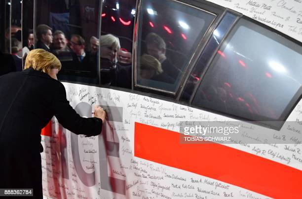 German Chancellor Angela Merkel signs a special ICE high speed train of German railway operator Deutsche Bahn after the train coming from Munich and...