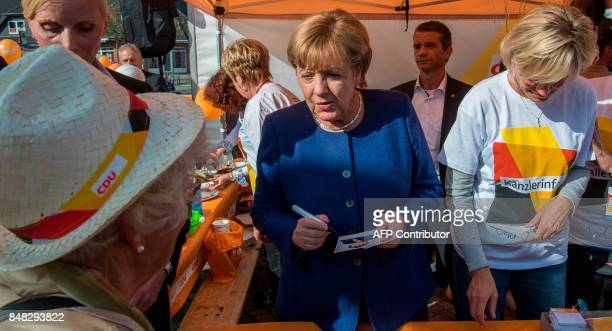 German Chancellor Angela Merkel signs autographs at a neighbourhood fair organised by the local branch of the Christian Democratic Union in Stralsund...