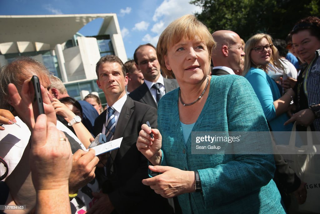German Chancellor Angela Merkel signs autographs for visitors during the annual open-house day at the Chancellery on August 25, 2013 in Berlin, Germany. Germany is facing federal elections scheduled for September 22 and so far the CDU has a substantial lead in polls over the opposition.