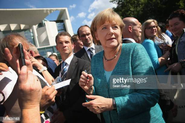 German Chancellor Angela Merkel signs autographs for visitors during the annual openhouse day at the Chancellery on August 25 2013 in Berlin Germany...