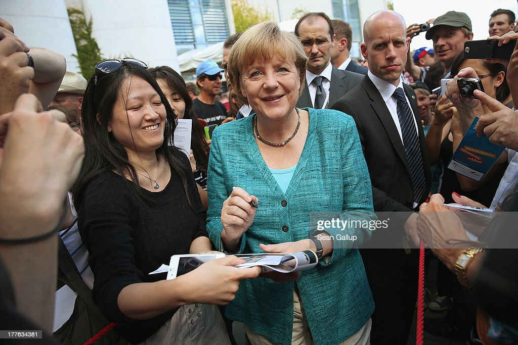 German Chancellor <a gi-track='captionPersonalityLinkClicked' href=/galleries/search?phrase=Angela+Merkel&family=editorial&specificpeople=202161 ng-click='$event.stopPropagation()'>Angela Merkel</a> signs autographs for visitors during the annual open-house day at the Chancellery on August 25, 2013 in Berlin, Germany. Germany is facing federal elections scheduled for September 22 and so far the CDU has a substantial lead in polls over the opposition.