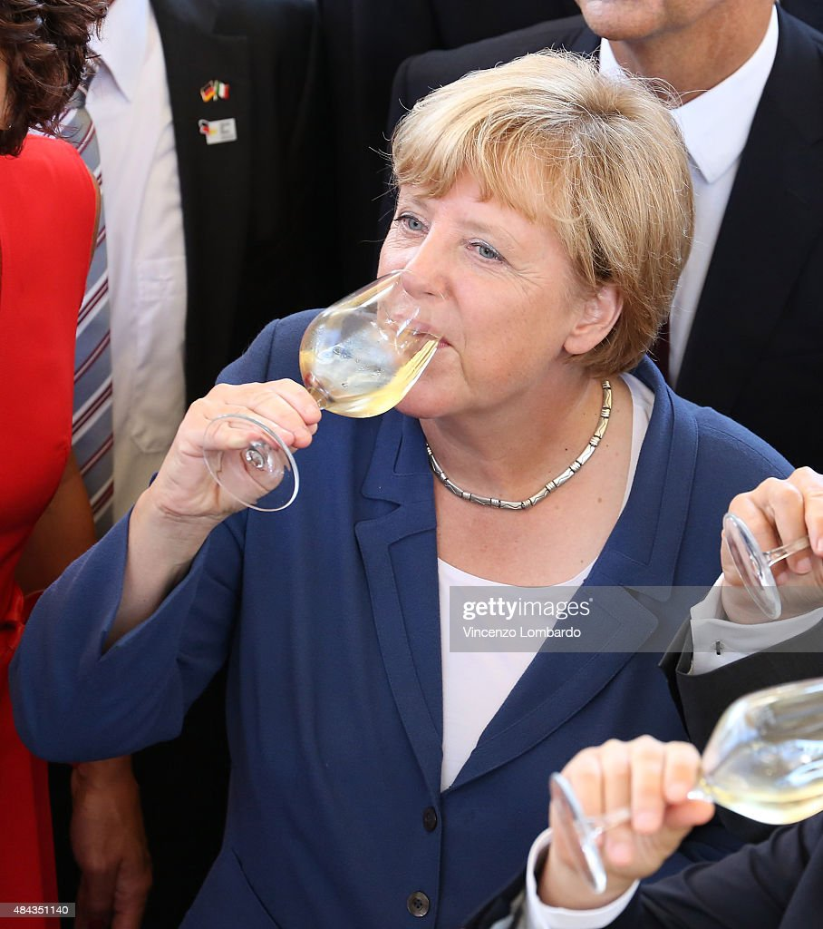 Angela Merkel visit German Chancellor Angela Merkel sips her drink during a visit to the Tyrol Pavilion at the
