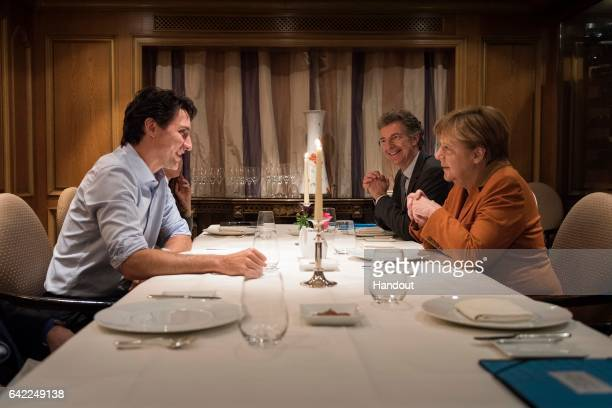 German Chancellor Angela Merkel sits across the table for dinner with Canadian Prime Minister Justin Trudeau and next to Christoph Heusgen German...