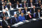 German Chancellor Angela Merkel sits between lawmakers of her Christian parties' block during the constituent session of the German parliament...