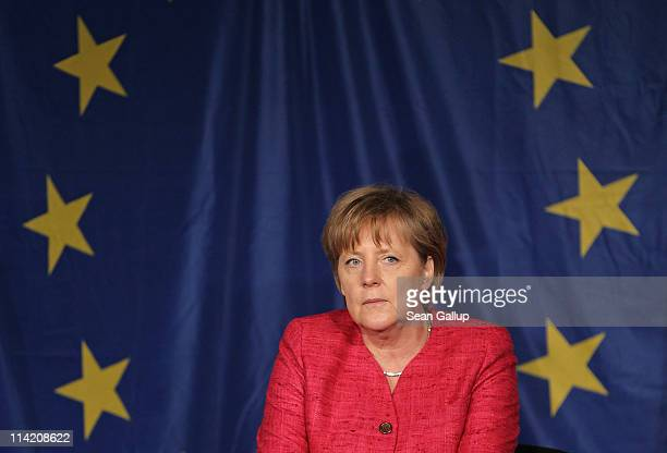 German Chancellor Angela Merkel sits in front of a flag of the European Union while visiting students at the Sophie Scholl school on the fifth...