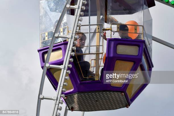 German Chancellor Angela Merkel sits with two children in a Ferris wheel as she continues on the election campaign trail in Stralsund on September 16...