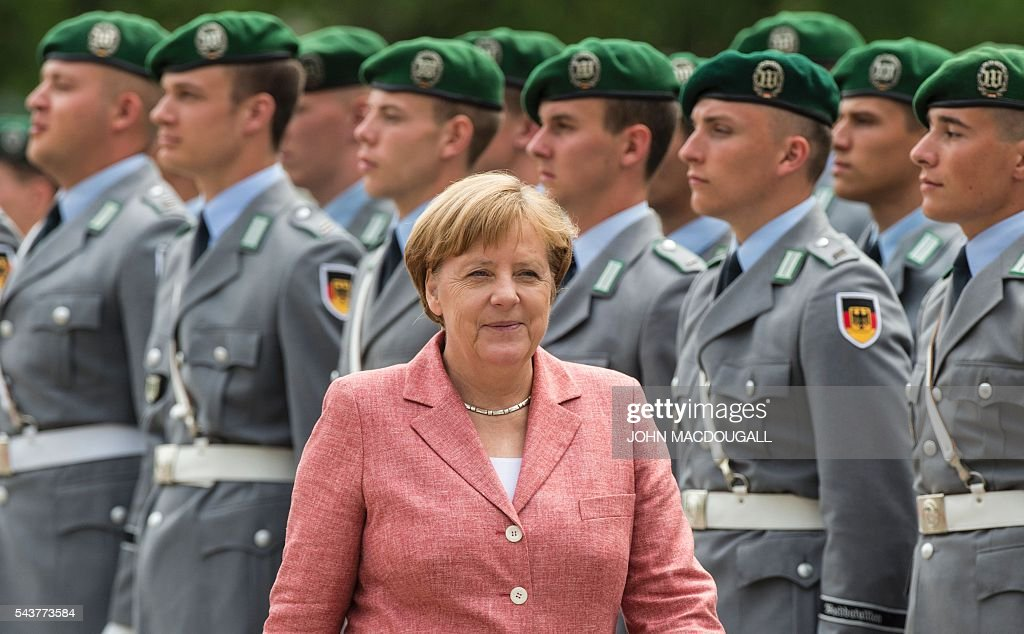 German Chancellor Angela Merkel smiles after greeting soldiers forming an honour guard before welcoming the members of the Presidency of Bosnia and Herzegovina at the chancellery in Berlin on June 30, 2016. / AFP / JOHN