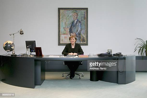 German Chancellor Angela Merkel smiles as she sit at her workroom infront of the Adenauer portrait Merkel receives from Norbert Lammert President of...