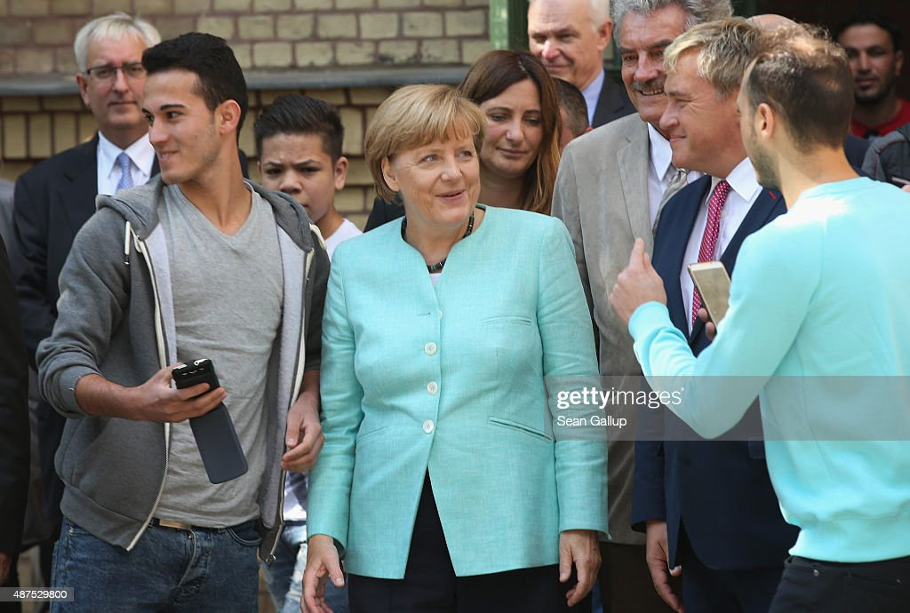 German Chancellor Angela Merkel smiles to a migrant asking for a selfie after she visited the AWO Refugium Askanierring shelter for migrants on September 10, 2015 in Berlin, Germany. Merkel visited several facilities for migrants today, including an application center for asylum-seekers, a school with welcome classes for migrant children and a migrant shelter. Thousands of migrants are currently arriving in Germany every day, most of them via the Balkans and Austria. Germany is expecting to receive 800,000 asylum applicants this year.