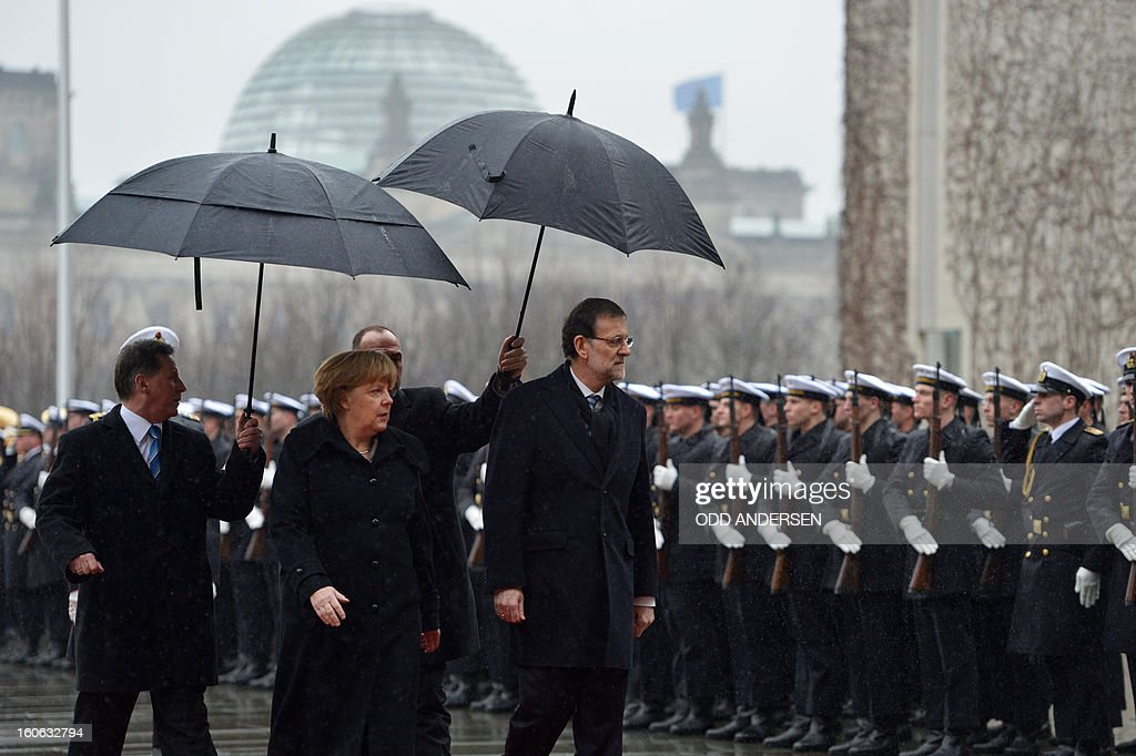 German Chancellor Angela Merkel (R) Spain's Prime Minister Mariano Rajoy inspect an honor guard upon his arrival at the Chancellery in Berlin on February 4, 2013 before their meeting. Merkel hosts for talks Rajoy, currently under fire for alleged corruption.