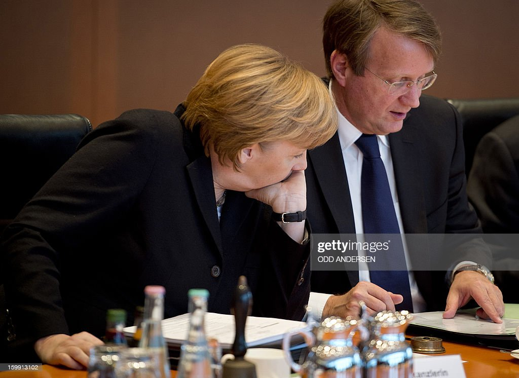 German Chancellor Angela Merkel (L) speak to Chief of staff Roland Pofalla at the weekly cabinet meeting at the Chancellery in Berlin on January 23, 2013.