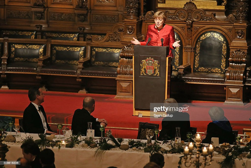 German Chancellor Angela Merkel speaks as British Prime Minister David Cameron (L) listens at the annual Matthiae-Mahl dinner at Hamburg City Hall on February 12, 2016 in Hamburg, Germany. The two leaders are there on the invitation of Hamburg Mayor Olaf Scholz, who reportedly saw the dinner as a gesture to show Germany's hope that Great Britain will remain in the European Union. The Matthiae-Mahl is a Hamburg tradition dating back to 1356 and began as a fest to welcome the spring season and also to honor a foreign official.