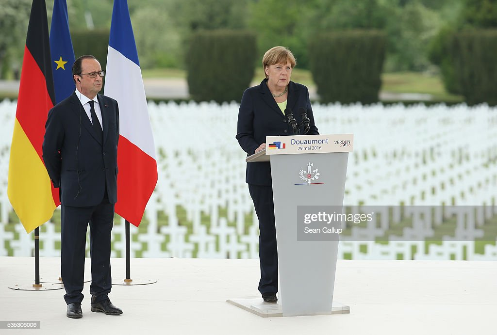 German Chancellor Angela Merkel speaks as French President Francois Hollande looks on during ceremonies to commemorate the 100th anniversary of the World War I Battle of Verdun at the Douaumont cemetery on May 29, 2016 near Verdun, France. The 1916, 10-month battle pitted the French and German armies against one another in a grueling campaign of trench warfare and artillery bombardments that killed a total of approximately 300,000 soldiers. The events today coincide with the 50th anniversary of commemorations held at Verdun by then French President Charles de Gaulle and German Chancellor Konrad Adenauer that paved the way for a new era of peaceful, post-war Franco-German relations.