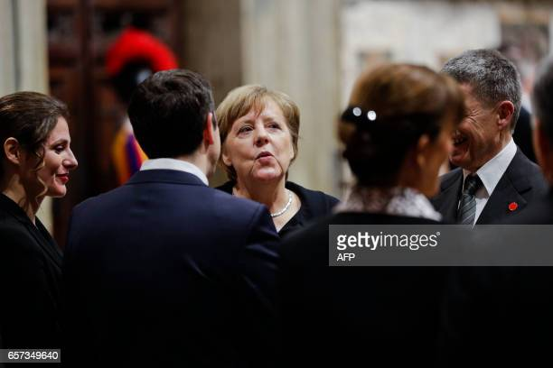 German Chancellor Angela Merkel speaks to Greece Prime Minister Alexis Tsipras back to camera as they wait for the start of an audience with Pope...