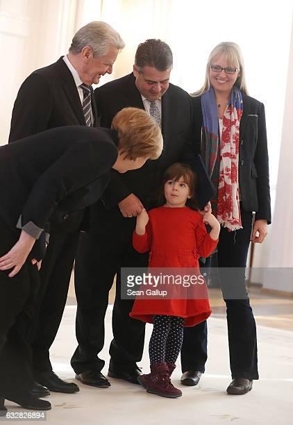 German Chancellor Angela Merkel speaks to Marie daughter of new German Foreign Minister Sigmar Gabriel as President Joachim Gauck and Gabriel's wife...