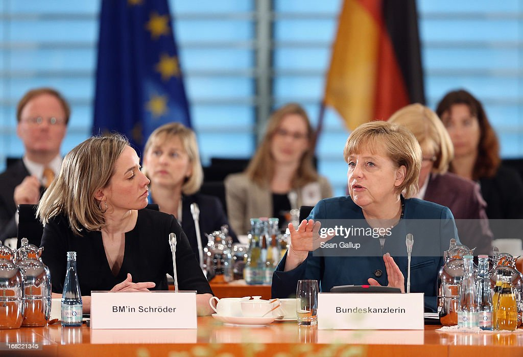 German Chancellor Angela Merkel (R) speaks to participants as German Family Minister Kristina Schroeder (L) looks on at a conference of women leaders hosted by Merkel at the Chancellery on May 7, 2013 in Berlin, Germany. German political parties are sparring over the introduction of quotas for a minimum number of women in senior management positions.
