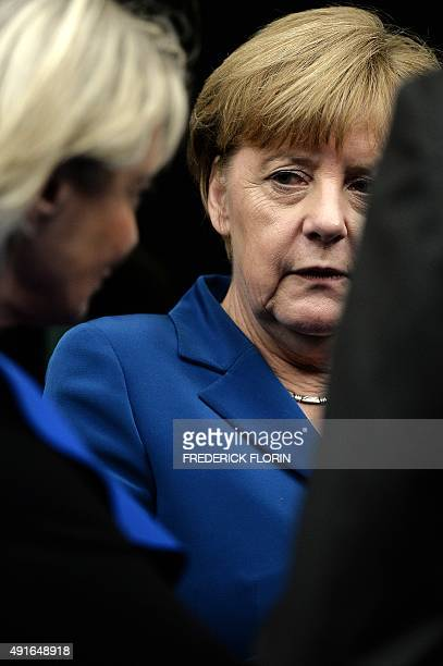 German Chancellor Angela Merkel speaks with delegates as she prepares to take her seat upon arrival at the European Parliament in Strasbourg eastern...