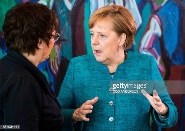 German Chancellor Angela Merkel speaks with economy minister Brigitte Zypries at the start of the weekly cabinet meeting at the Chancellery in Berlin...