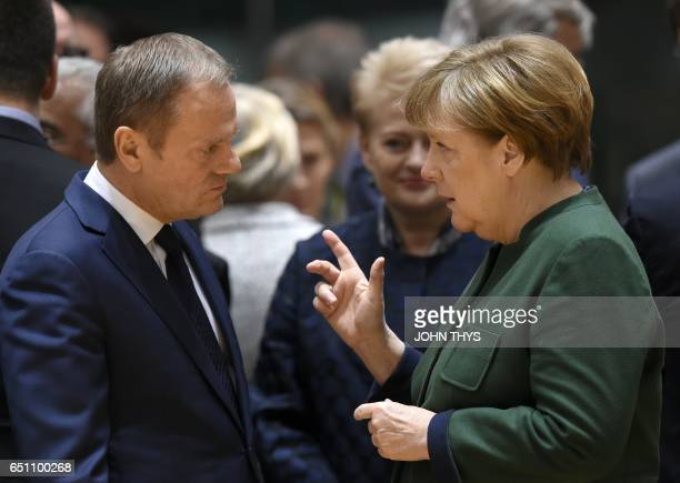 German Chancellor Angela Merkel speaks with European Council president Donald Tusk on the second day of a European Summit at the Europa Building at...