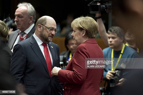 German Chancellor Angela Merkel speaks with European Parliament president Martin Schulz before a roundtable meeting during an EU Council summit at...