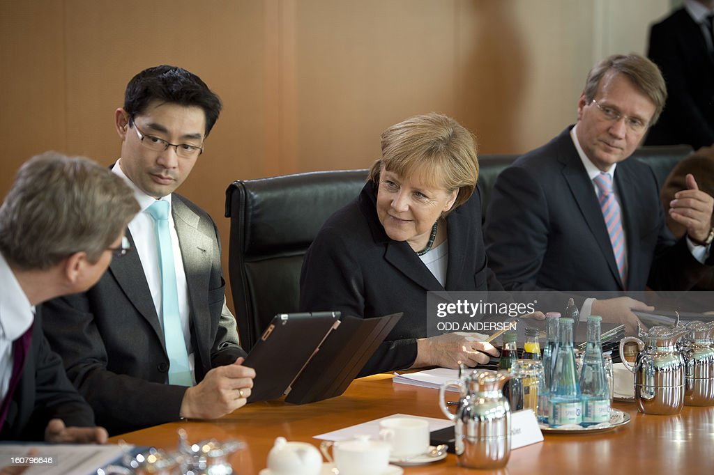 German Chancellor Angela Merkel (2ndR) speaks with foreign minister Guido Westerwelle (L) seated between her chief of staff Roland Pofalla (R) and Economy minister Phllipp Roesler (2ndL) during the weekly cabinet meeting at the Chancellery in Berlin on February 6, 2013.