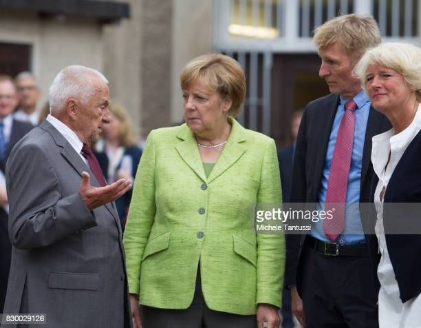 German Chancellor Angela Merkel speaks with former Prisoner Arno Defke as she visits the former prison of the East German communistera secret police...