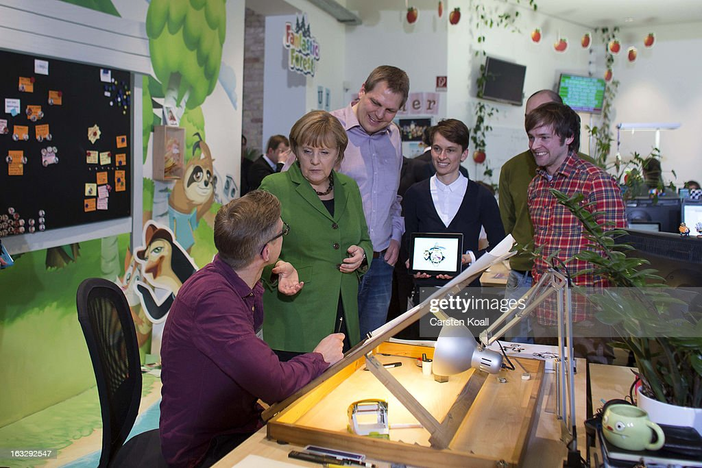 German Chancellor Angela Merkel (2nd L) speaks with graphic artist Gerben Steenks (L), during guided tour by the general manager Jens Begemann (C) in the Wooga company, which makes social games for smartphones and tablets, on March 7, 2013 in Berlin, Germany. Berlin has drawn a significant number of startup companies in recent years, many of which are drawn by the city's hip reputation and its comparatively low cost of living.