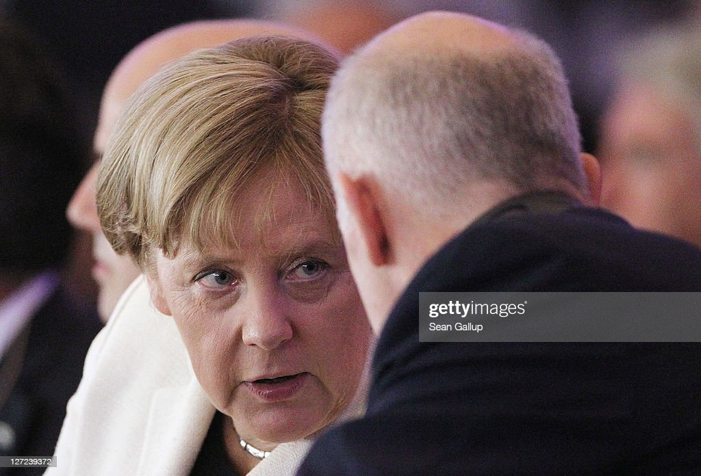 German Chancellor Angela Merkel speaks with Greek Prime Minister George Papandreou at a convention of the Federation of German Industry (BDI), where Papandreou spoke in an appeal for more German investment in Greece, on September 27, 2011 in Berlin, Germany. Papandreou and Merkel are scheduled to meet at the Chancellery later in the day to discuss the current Greek debt crisis that is threatening the stability of the Euro.