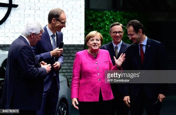 German Chancellor Angela Merkel speaks with Michael Lohscheller CEO of Opel Opel's CFO Philippe de Rovira the president of the German Automobile...